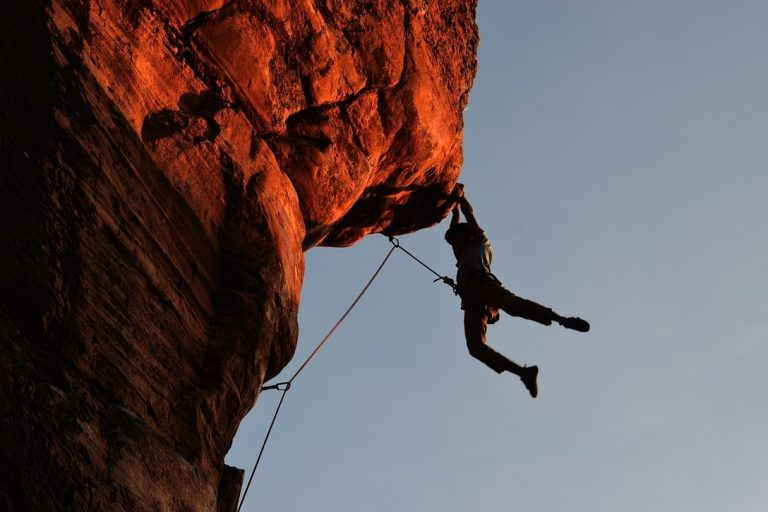 Male climber hanging from a cliff at sunset
