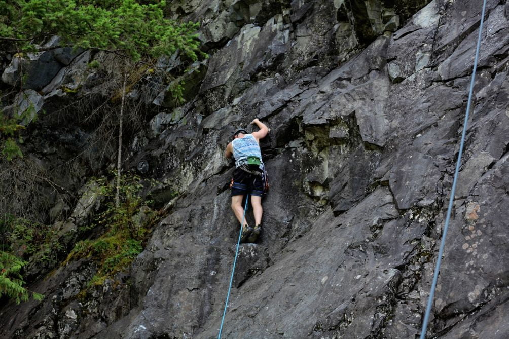 man climbing a dark rock wall with vegetation and ropes
