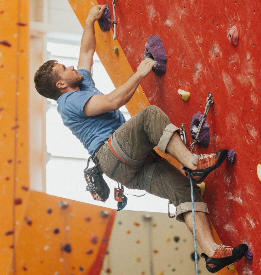 man climbing an indoor climbing wall