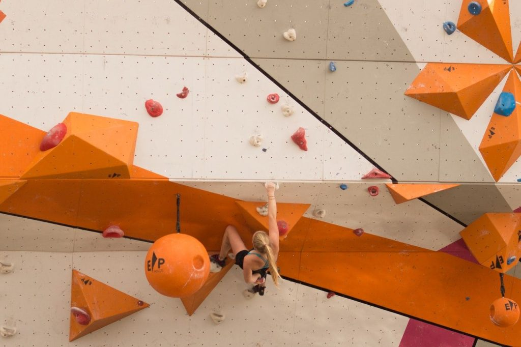 woman climbing an indoor climbing wall