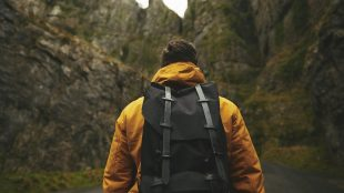 Man hiking with a backpack and a mustard hiking jacket