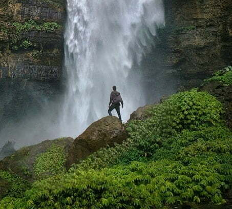 Man standing in front of a waterfall on a grassy hill