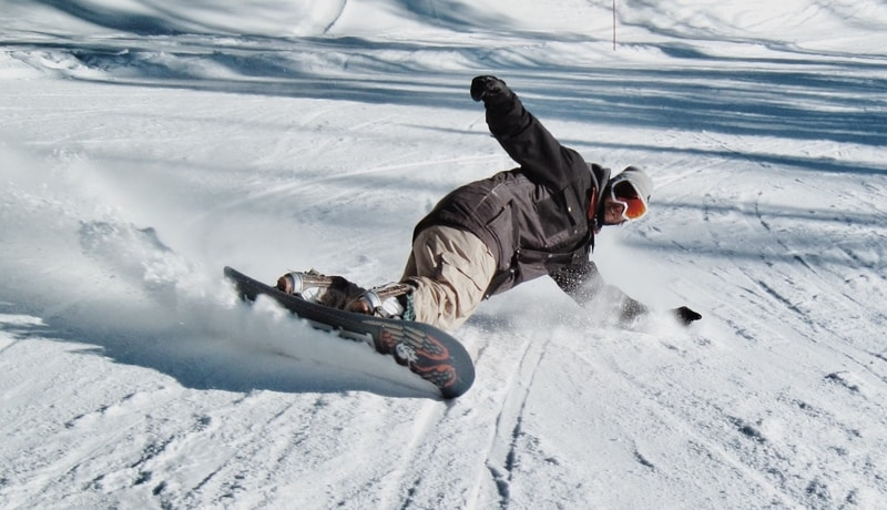 Skidding snowboarder in snow