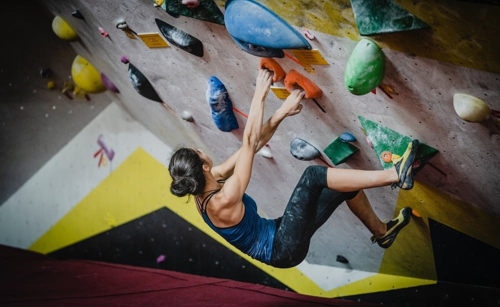 A woman breaking in her climbing shoes at a climbing gym