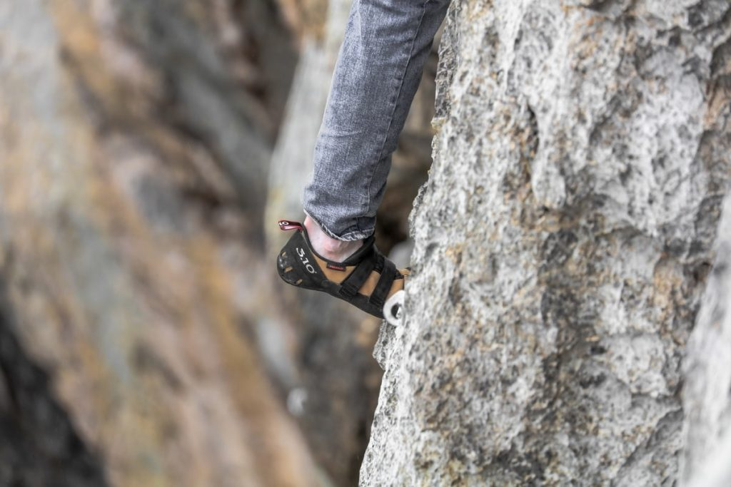 Person wearing grey jeans rock climbing