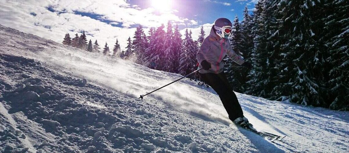 Woman skiing down a slope with ski helmet headphones